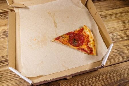 Last slice of pizza in cardboard box on a wooden table. Concept for home delivery of food, fast food, delivery of pizza 写真素材 - 134956859