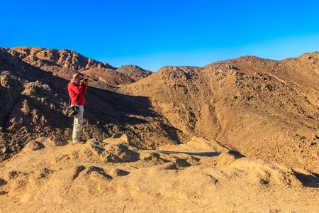 Young man taking a photos of mountain range Red Sea Hills in Arabian desert, Egypt. Travel photography concept Standard-Bild