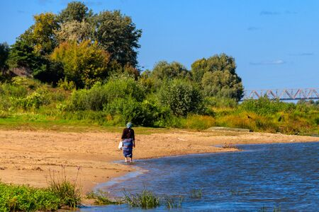 Young woman walking along a bank of the Oka river in Russia. Rear view