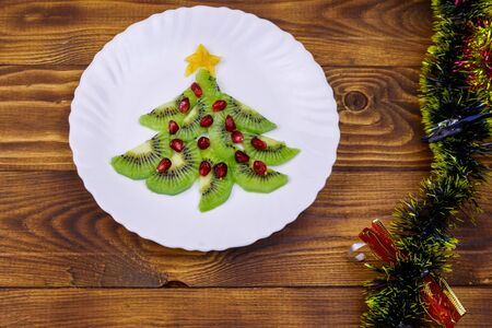 Christmas tree made of kiwi slices and pomegranate and Christmas decor on wooden table. Top view. Creative idea for Christmas and New Year festive desserts. Funny food idea for kids