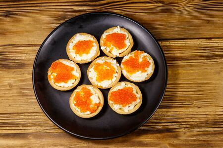 Tartlets with red caviar and soft cheese on a wooden table. Top view