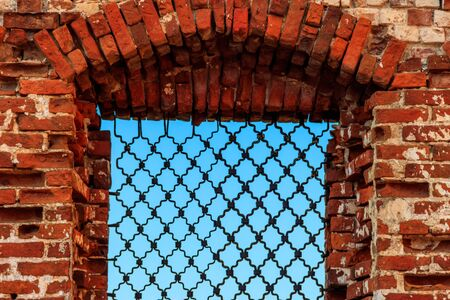 Window with iron grating in a wall of ancient red brick building 写真素材