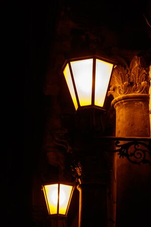 Lighted vintage street lantern on the wall of a house at night