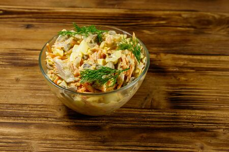 Tasty salad with chicken breast, roasted mushrooms, carrots, grated cheese, eggs and mayonnaise on wooden table