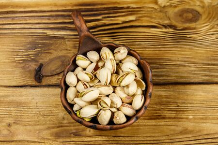 Pistachio nuts in ceramic bowl on a wooden table. Top view