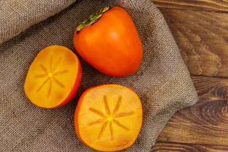 Tasty ripe persimmon fruits on a wooden table 写真素材