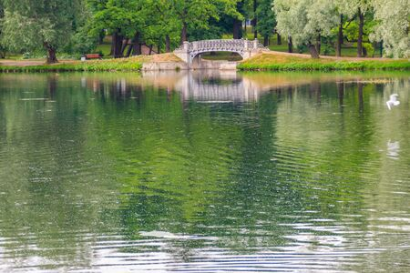 Lake with old bridge in a park in Gatchina, Russia