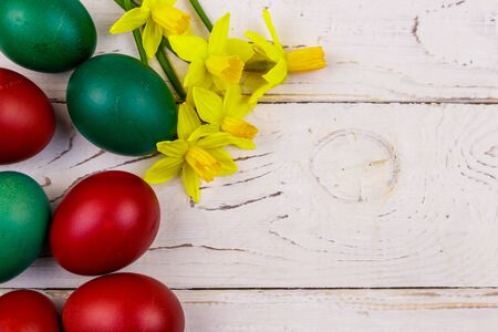 Painted Easter eggs and yellow daffodils on white wooden background. Easter composition. Top view, copy space