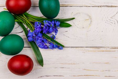 Painted Easter eggs and blue scilla flowers on white wooden background. Easter composition. Top view, copy space 写真素材