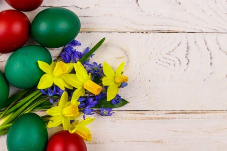Painted Easter eggs and bouquet of yellow daffodils and blue scilla flowers on white wooden background. Easter composition. Top view, copy space