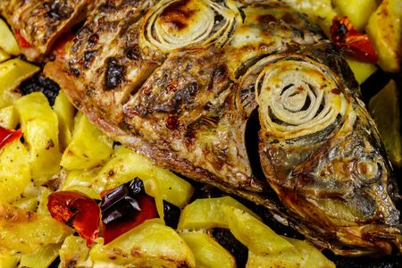 Baked carp with potatoes in a baking dish