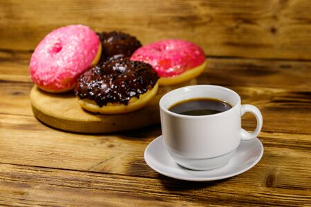 Cup of coffee and tasty donuts on a wooden table