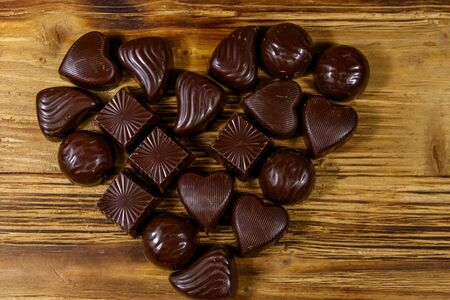 Heart shape made of different chocolate candies on wooden table. Top view. Valentine Day concept