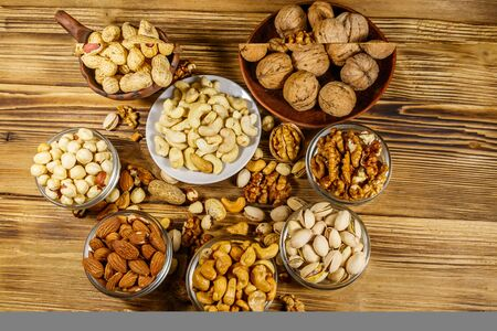 Assortment of nuts on wooden table. Almond, hazelnut, pistachio, peanut, walnut and cashew in small bowls. Top view. Healthy eating concept