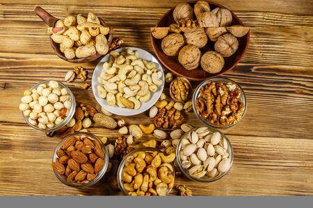 Auswahl an Nüssen auf Holztisch. Mandel, Haselnuss, Pistazie, Erdnuss, Walnuss und Cashew in kleinen Schälchen. Ansicht von oben. Konzept für gesunde Ernährung