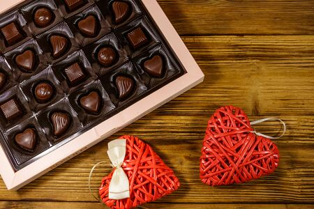 Assorted chocolate candies in a box and two red hearts on wooden table. Top view. Valentine Day concept