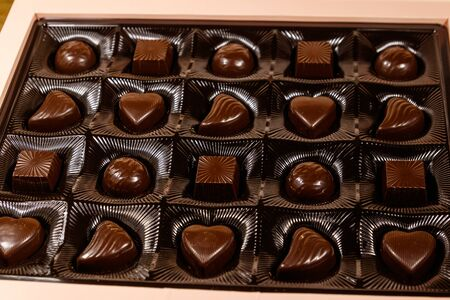 Assorted chocolate candies in a box. Close-up