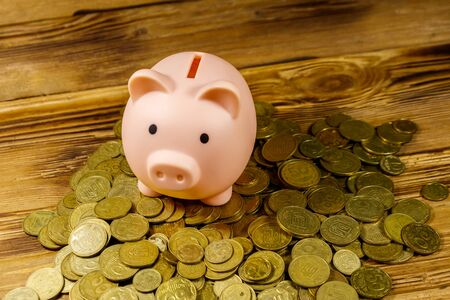 Pink piggy bank on a heap of coins on wooden background. Saving money concept Stockfoto