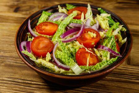 Insalata sana con verza, pomodorini, cipolla rossa e olio d'oliva su tavola di legno wooden