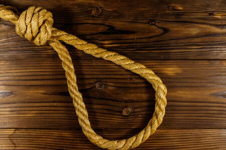 Deadly loop of rope on a wooden background. Concept of death penalty or suicide Stock Photo