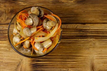 Delicious marinated mushrooms with carrot, onion and spices in glass bowl on wooden table. Top view Banco de Imagens - 140803711