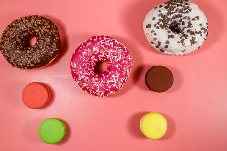 Tasty donuts and macaroons on pink background. Top view 스톡 콘텐츠