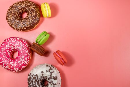 Tasty donuts and macaroons on pink background. Top view, copy space