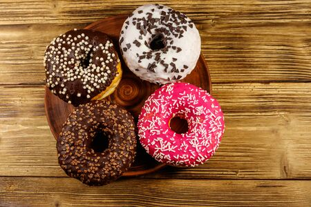 Tasty donuts on a wooden table. Top view
