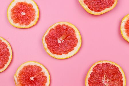Slices of grapefruit on a pink background