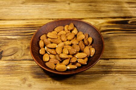 Almonds in ceramic plate on a rustic wooden table