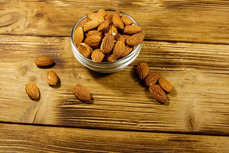 Almonds in glass bowl on a rustic wooden table