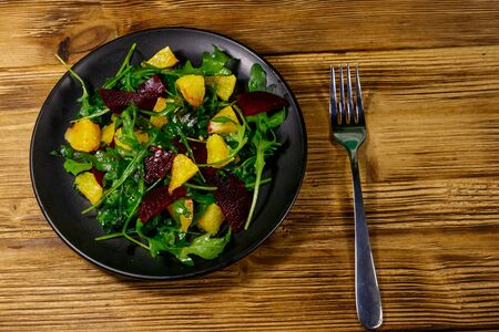 Tasty salad of fresh arugula, beetroot and oranges on wooden table. Top view. Healthy food or vegetarian concept