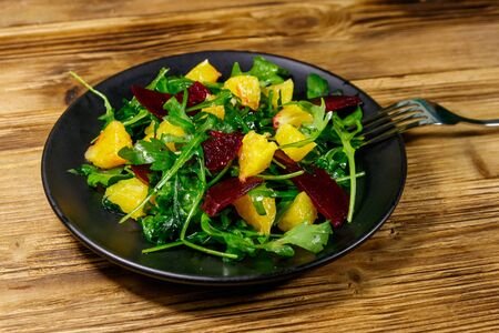 Tasty salad of fresh arugula, beetroot and oranges on wooden table. Healthy food or vegetarian concept