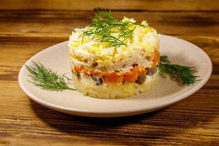 Tasty layered salad with potatoes, chicken breast, marinated mushrooms, carrots, eggs and mayonnaise on wooden table 스톡 콘텐츠