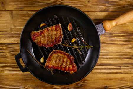 Grilled pork steaks with rosemary, garlic and spices in cast iron grill frying pan on wooden table. Top view 스톡 콘텐츠