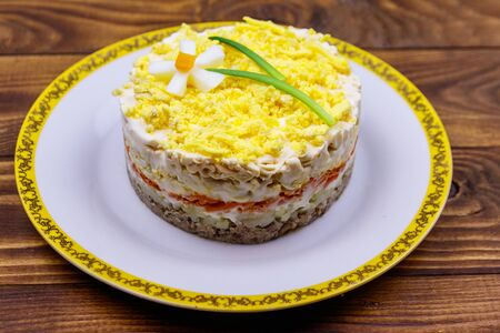 Traditional russian layered salad Mimosa with spring decoration Daffodil. Decoration is made of egg, green onion and carrot