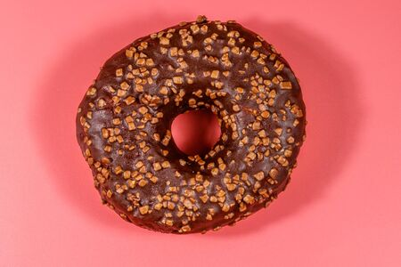 Tasty chocolate donut on a pink background