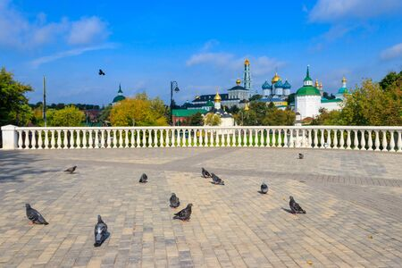 Flock of pigeons on a viewing platform with view of Trinity Lavra of St. Sergius in Sergiev Posad, Russia Banco de Imagens