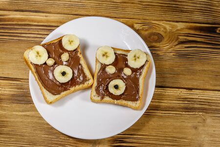 Two sweet sandwiches with delicious chocolate hazelnut spread and banana in shape of bear on wooden table. Top view