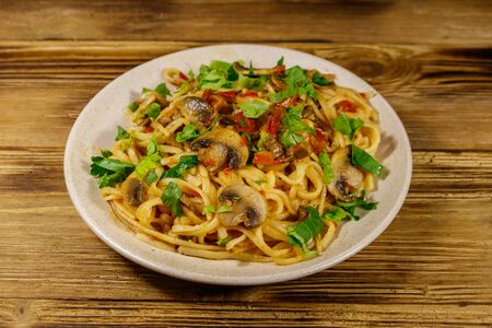 Pasta with mushrooms and tomato sauce on wooden table 스톡 콘텐츠