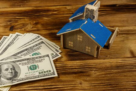 House model and U.S. one hundred dollar bills on wooden background. Property investment, home loan, house mortgage, real estate concept Banco de Imagens