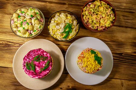 Set of festive mayonnaise salads on wooden table. Top view Banco de Imagens