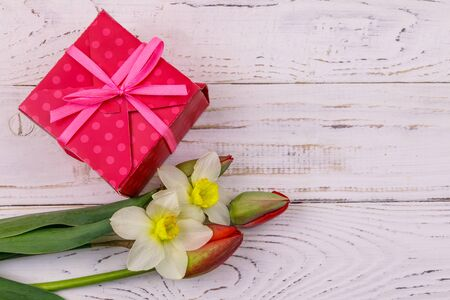 Gift box and bouquet of red tulips and daffodils on white wooden background. Top view, copy space