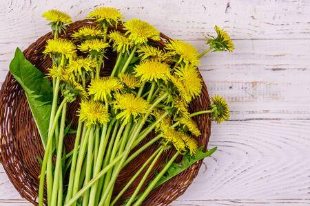 Yellow dandelion flowers in wicker basket on white wooden background. Top view Banco de Imagens