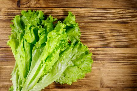 Fresh green lettuce leaves on wooden table. Top view