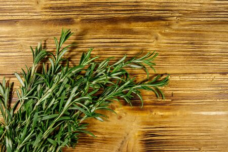 Fresh rosemary herbs on a wooden table. Top view Banco de Imagens
