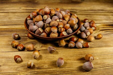 Hazelnuts in ceramic plate on a wooden table Stockfoto