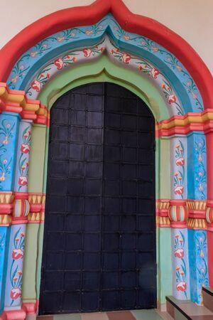 Ancient russian architecture. Close-up of arched metal door in russian style