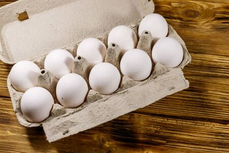 Raw chicken eggs in cardboard egg box on wooden table