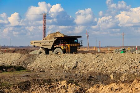 Huge yellow mining dump truck working in iron ore quarry. Mining industry Stock Photo